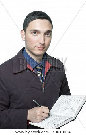 man in jacket writing in his planner