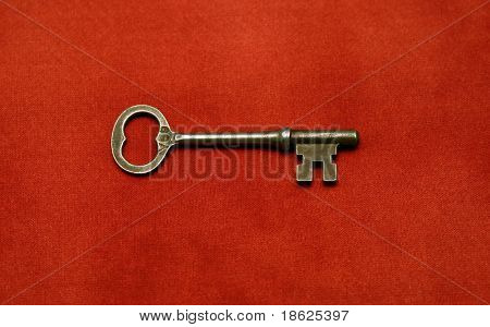 Antique key on red cloth