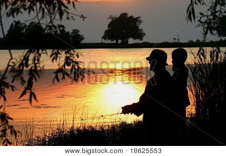 Father and son fishing at dusk.