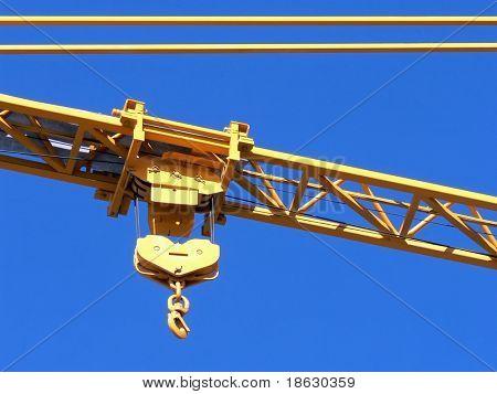 El gancho de una grúa de construcción contra un cielo azul.