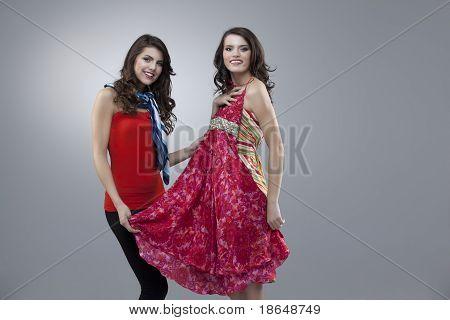 Vestem felizes duas mulheres tentando flor vermelha