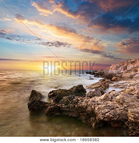 Sea and rock at the sunset. Nature composition.