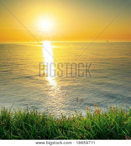 Sundown composition. Sky, sea, and green grass.