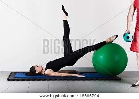 Hip extension  with ball position. Pilates gymnastics is a Germanic evolution of yoga, used by athletes to improve flexibility and body fitness and by chiropractors for patient recovery.