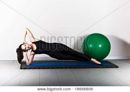 Side plank with ball position. Pilates gymnastics is a Germanic evolution of yoga, used by athletes to improve flexibility and body fitness and by chiropractors for patient recovery.