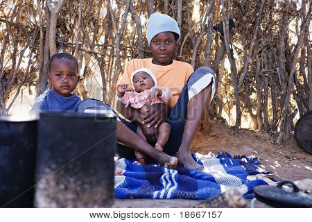 Portrait of African children and mother in the hut, location Mankodi village, Botswana