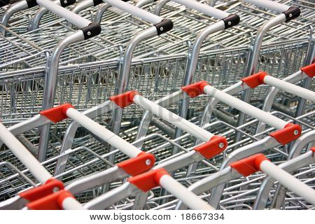 two rows of aligned shopping carts with red and black handles