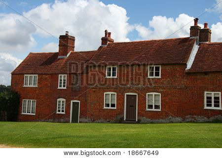 Historic English terraced village house with green lawn and blue sky, 18th century