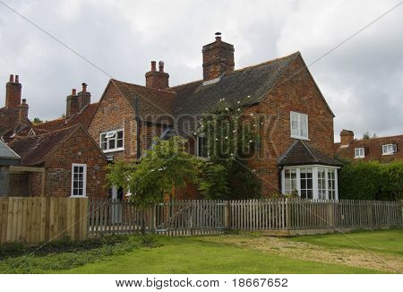 Historic English village house with green lawn, 18th century