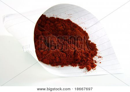 pinch of paprika in a cone of paper on white