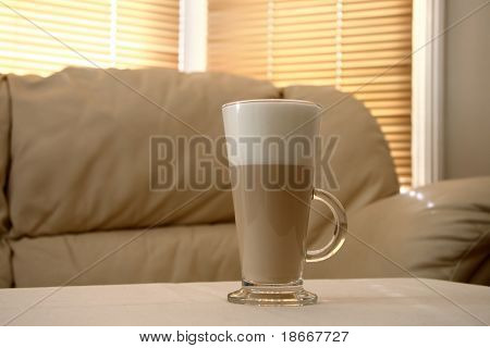 Cafe Coffee Latte in a tall glass and creamy sofa on background, soft focus