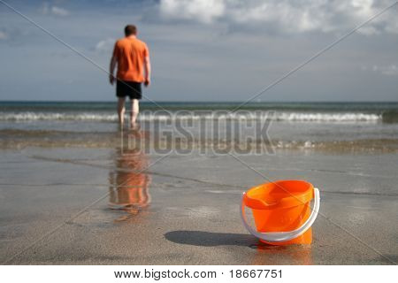 brigh orange sand bucket with water on the beach and boy on the background