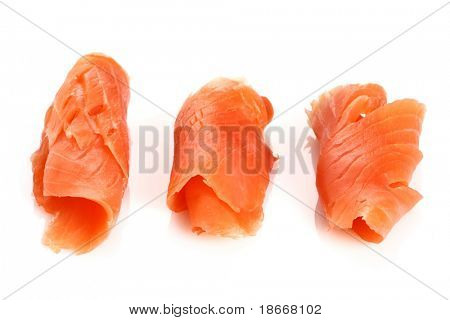 three pieces of smoked fish salmon on white, light shadow