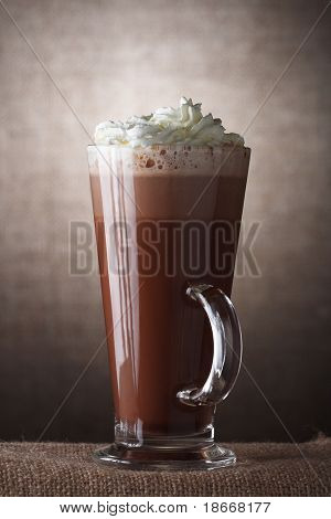 Hot Chocolate with cream in Tall Glass on brown rustic background, Low Key  Lighting Technique