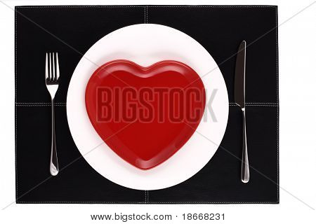 empty white and red heart plates with a knife and fork on a black leather place mat