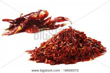 pile of Hot Red Chilli Chillies pepper, dried and crushed. Second pile of Whole chillies on background. Shallow DOF, isolated on white