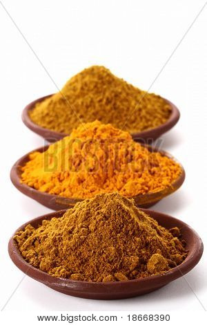 piles of bright Curry Powder and tumeric in teraccotta dish on white, shallow DOF, focus on the first one.
