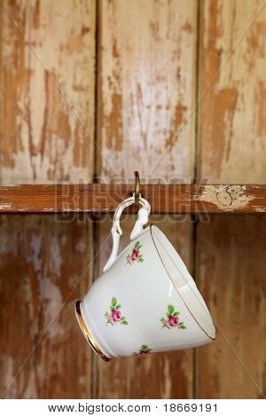 tea cup hanging on a hook in old wooden cupboard, shallow DOF
