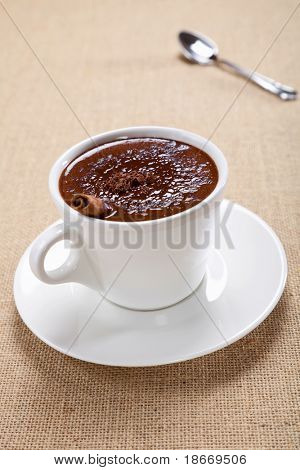hot chocolate in white mug with cinnamon stick, saucer and spoon, on jute backdrop