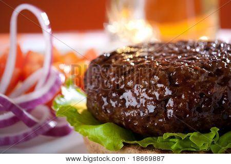hambúrguer de carne com cebola e cerveja no fundo, DOF raso