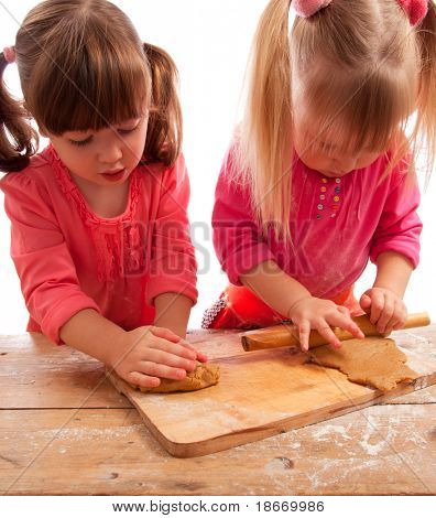 two busy little girls kneading and rolling gingerbread dough