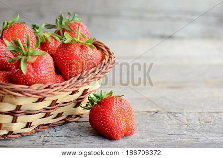 Fresh strawberries. Ripe juicy strawberries in a wicker basket and on a vintage wooden table. Natural source of vitamins and minerals. Closeup picture