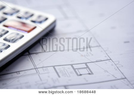 Calculator and house plan blueprints close up , shallow DOF photo