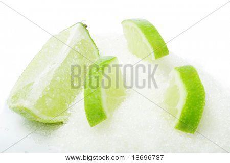 sliced ripe fresh lime in shugar on white background