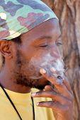 foto of rastafari  - Rastafarian man smoking cannabis - JPG