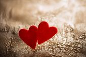 two fluffy hearts on cracked painted background, shallow DOF, backlit poster