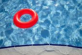 floating orange ring on edge of swimpool with waves reflecting in the summer sun