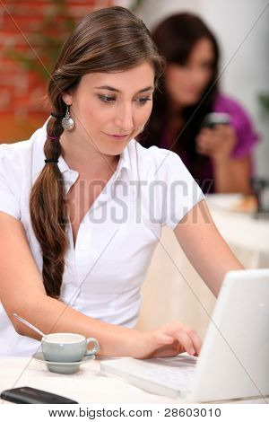Woman working on her laptop in a cafe