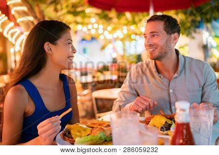 poster of Couple eating hamburgers at outdoor restaurant terrace happy tourists on summer vacation. Florida tr
