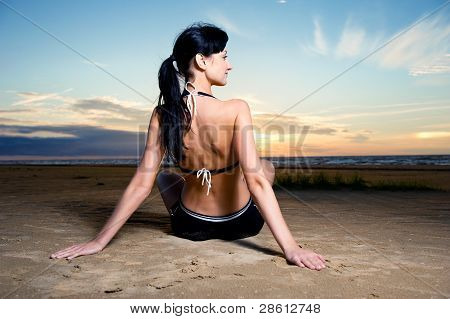 Young Brunette Sitting On The Beach Near The Sea
