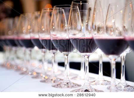 Glasses Of Red Wine In A Row On A Table