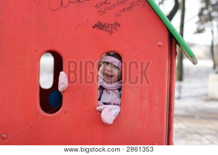 Little Girl Play Hide-And-Seek At The Kindergarten Playground