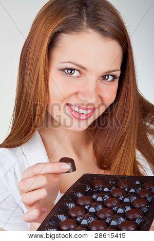 Beautiful Young Woman Eating Chocolates