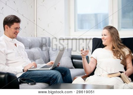Home scene. Man working at laptop, pregnant woman sitting at armchair and relaxing