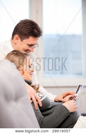 Pregnant wife and her husband looking at photos from ultrasound investigation