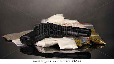 Cocaine and marihuana in packages and handgun on grey background