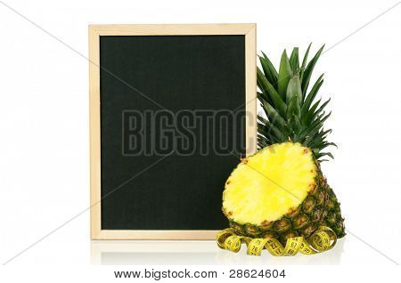 Fresh ripe pineapple with a blackboard and measure tape over white background