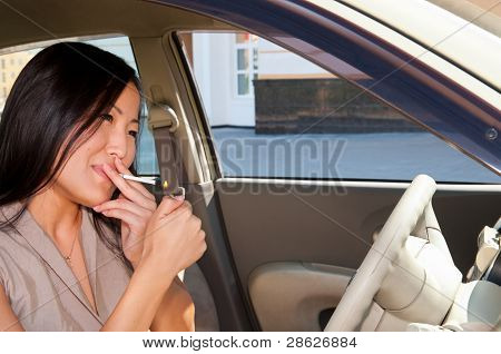 Young Woman Lights A Cigarette