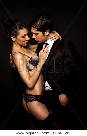Businessman With Sexy Woman In Lingerie in intimate pose, dark studio portrait on black