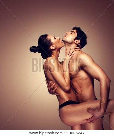 Erotic Couple Embracing, naked except for panties, womans leg obscuring loins, studio on brown with copy space