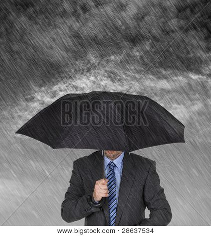 Businessman with umbrella protecting himself from the storm concept for protection from recession or economic depression etc