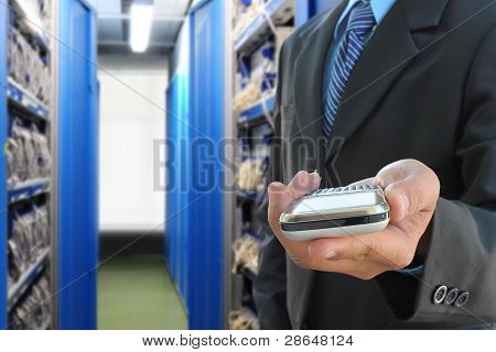 businessman hand holding mobile phone in the communication and internet network server room