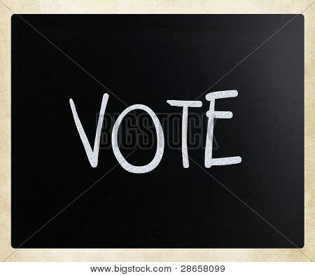 The Word 'vote' Handwritten With White Chalk On A Blackboard