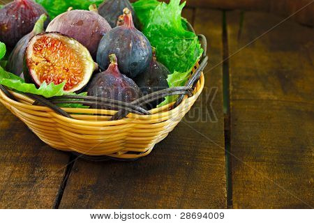 Basket Of Ripe Figs In A Basket On Bed Of Leaves