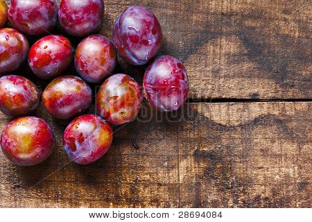 Fresh Plums On Old Wooden Table