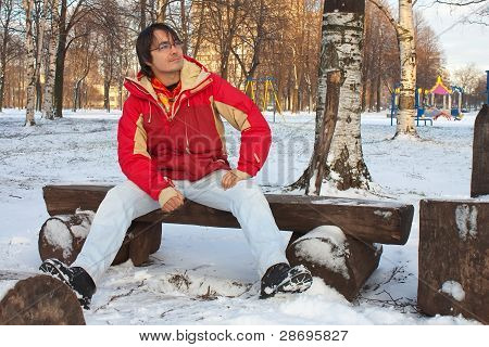 Young Man Sitting On Bench In Winter Park